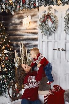 Mooie vrouw en haar schattige zoontje in kerstkleren poseren in versierd interieur.