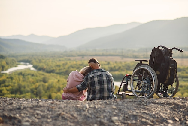 Mooie vrouw en haar wilsonbekwame echtgenoot rusten samen in de buurt van zijn rolstoel op de heuvel.