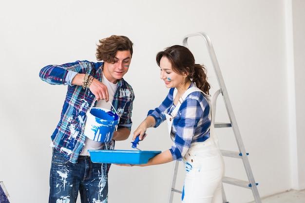 Mooie vrouw en knappe man schildert de muur in nieuw appartement.