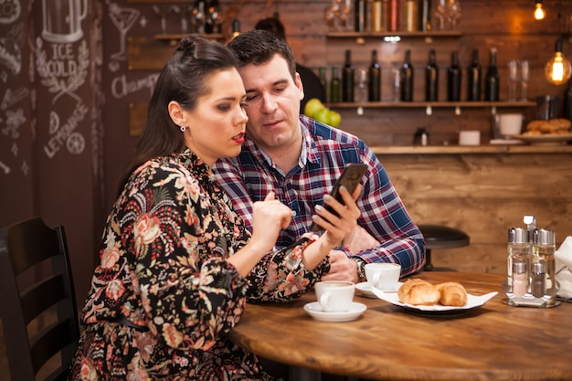 Mooie vrouw en man kijken naar de telefoon tijdens het eten. hippe kroeg.