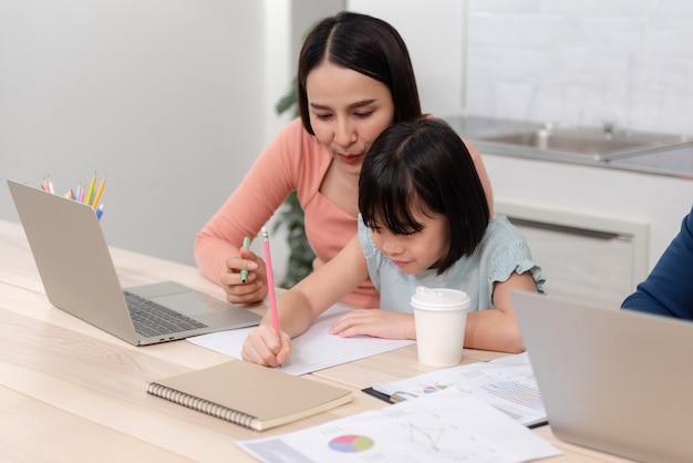 Mooie vrouw en schattige aziatische meisjes tekenen en schrijven op wit papier de knappe man werkt online.