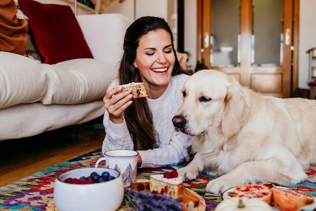 Mooie vrouw en schattige golden retrieverhond die van gezond ontbijt genieten thuis, liggend op de vloer. gezond ontbijt met thee, fruit en snoep.