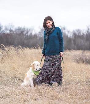 Mooie vrouw en schattige hond aan de leiband wandelen in de natuur