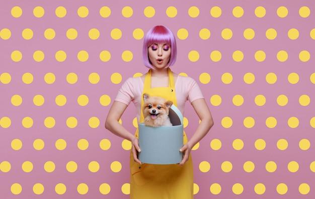 Mooie vrouw en schattige pluizige puppy van pommeren spitz op trendy roze polka dot achtergrond