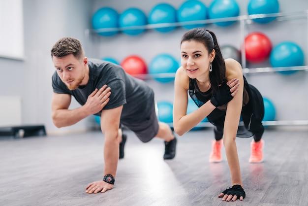 Mooie vrouw en sterke man doet push-ups aan de ene kant