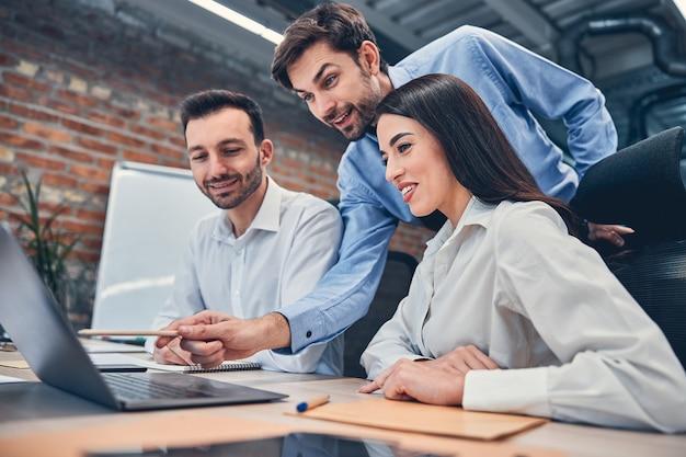 Mooie vrouw en twee bebaarde man kijken naar het scherm van de laptop terwijl hij zijn project bespreekt