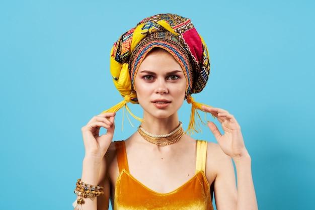 Mooie vrouw etniciteit veelkleurige hoofddoek make-up glamour blauwe achtergrond