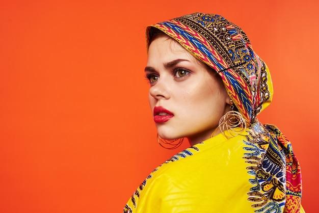 Mooie vrouw etniciteit veelkleurige hoofddoek make-up glamour rode achtergrond