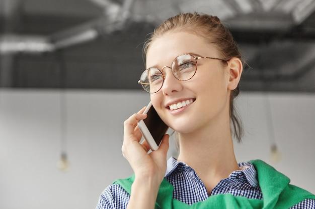 Mooie vrouw formeel gekleed in kantoor met telefoon
