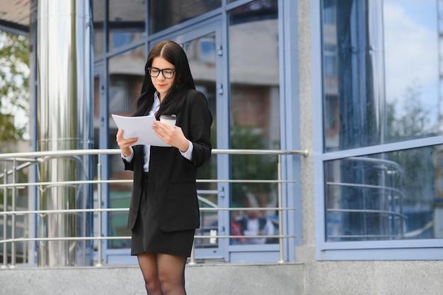 Mooie vrouw gaan werken met koffie wandelen in de buurt van kantoorgebouw