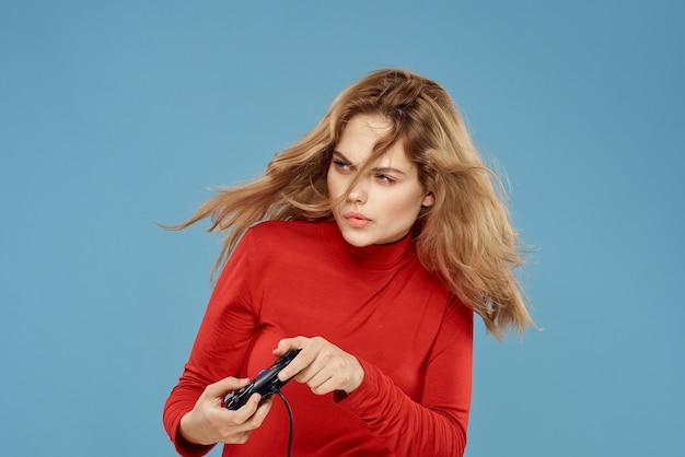 Mooie vrouw gamepad in handen spelen van games entertainment consoles tot blauwe ruimte rode jas levensstijl