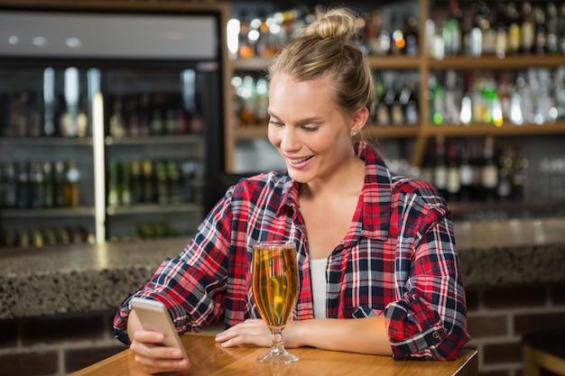 Mooie vrouw gebruikend smartphone en hebbend een bier