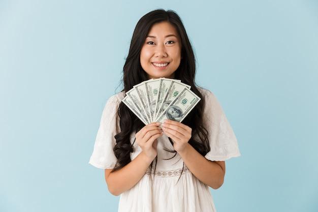 Mooie vrouw geïsoleerd over het blauwe geld van de muurholding