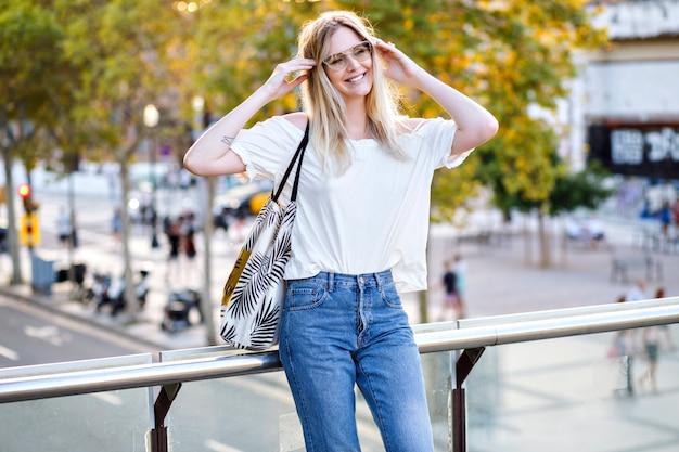 Mooie vrouw, gekleed in casual outfit en haar studententas, poseren op straat en genieten van hete zonnige zomerdag