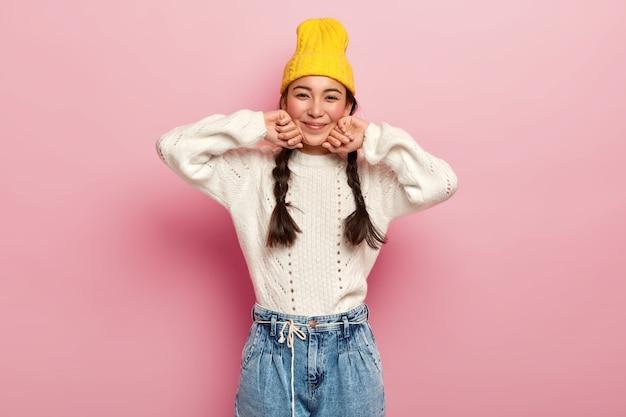 Mooie vrouw gekleed in een modieuze gele hoed, witte trui en spijkerbroek, heeft een enthousiaste en charmante blik in de camera, blije uitdrukking, geïsoleerd over roze muur