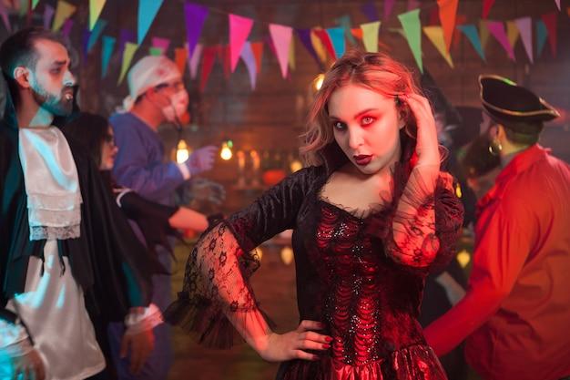 Mooie vrouw gekleed in een zwarte jurk voor halloween-feest met een enge make-up. meisje met een enge kijken naar halloween-feest.