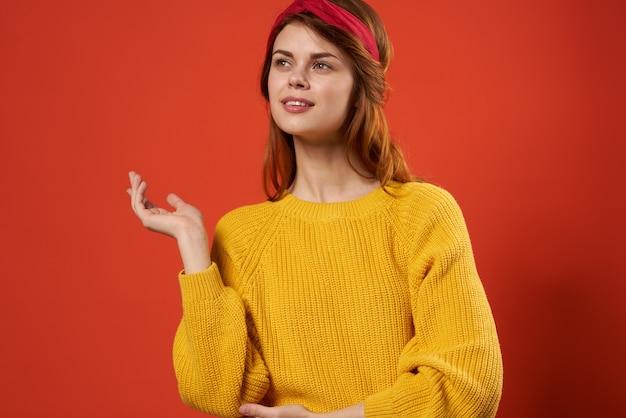 Mooie vrouw, gekleed in gele trui rode hoofdband hippie straatstijl rood.