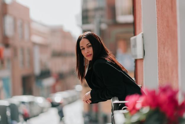Mooie vrouw gekleed in het zwart kijken naar de camera op een balkon met bloemen