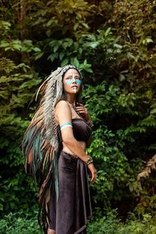 Mooie vrouw, gekleed in hoofdtooi gemaakt van veren van vogels. blauwe kleur geschilderd op haar wang
