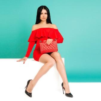 Mooie vrouw, gekleed in rode jurk met tas handtas met hoge hakken schoenen zittend op de witte bank