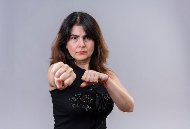 Mooie vrouw, gekleed in zwarte blouse die boos doet boksen en