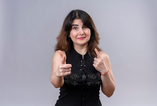 Mooie vrouw, gekleed in zwarte blouse glimlachend in vergelijking met wijsvingers