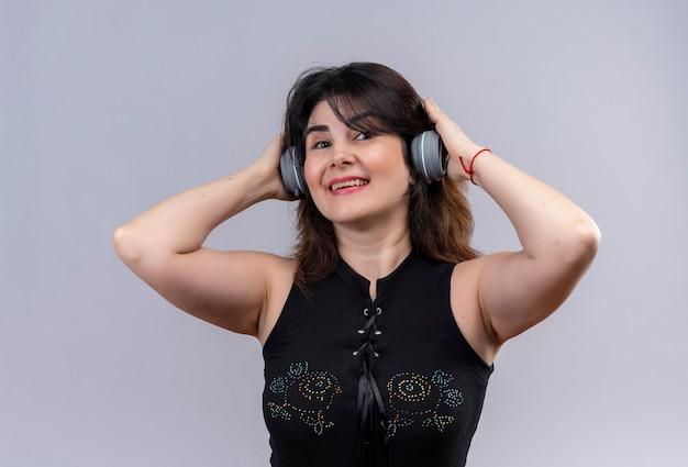 Mooie vrouw, gekleed in zwarte blouse op zoek energiek luisteren naar muziek met een koptelefoon