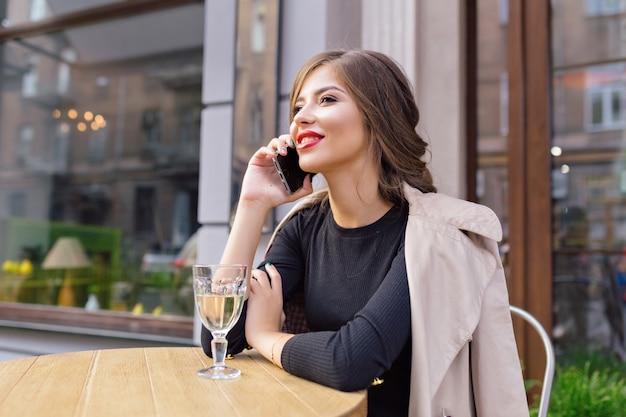 Mooie vrouw gekleed in zwarte jurk en beige loopgraaf met stijlvol kapsel en rode lippen op een terras, praten over de telefoon