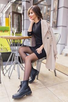 Mooie vrouw gekleed in zwarte jurk en beige loopgraaf met stijlvol kapsel en rode lippen op een terras