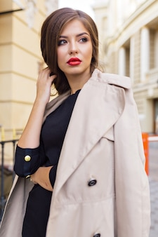 Mooie vrouw gekleed in zwarte jurk en beige loopgraaf met stijlvol kapsel en rode lippen op straat