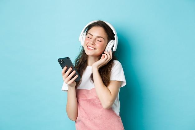 Mooie vrouw geniet van lied in koptelefoon, sluit ogen en glimlach terwijl ze naar muziek luistert in koptelefoon, smartphone in de hand houdend, staande over blauwe achtergrond.