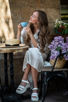 Mooie vrouw genieten van de koffie in de ochtend in de buurt van lila bloesem. leuk model en bloemen. aromatherapie en lenteconcept. meisje drinkt koffie bij coffeeshop.