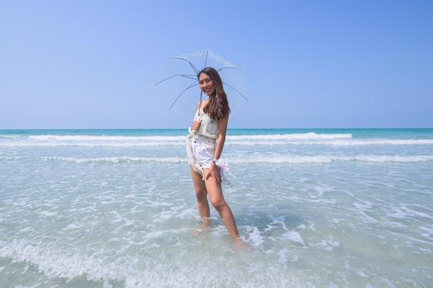 Mooie vrouw genieten van het strand met een paraplu