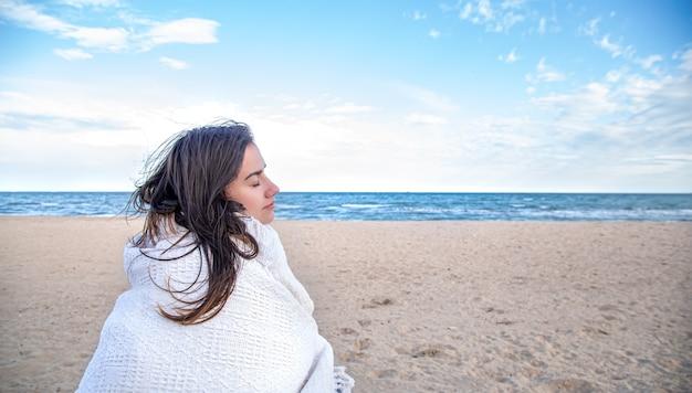 Mooie vrouw gewikkeld in een deken kijkt in de verte op het strand.