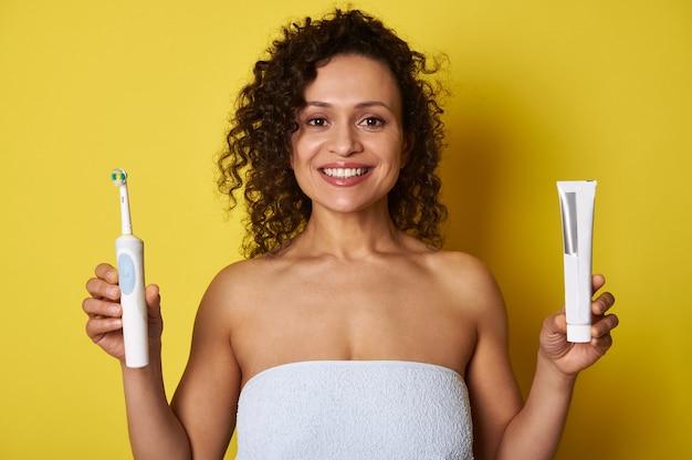 Mooie vrouw gewikkeld in een witte badhanddoek met een tandpasta in de ene hand en een elektrische tandenborstel in de andere hand