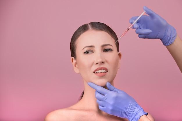 Mooie vrouw gezicht en schoonheidsspecialiste handen met spuit. arts maakt cosmetische injectie in de bovenlip. schone schoonheid concept