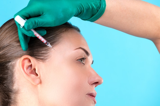 Mooie vrouw gezicht en schoonheidsspecialiste handen met spuit. arts maakt cosmetische injectie. schone schoonheid concept