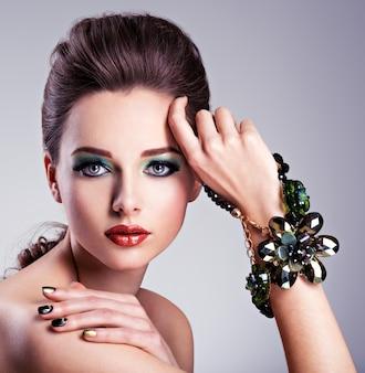 Mooie vrouw gezicht met mode groene make-up en sieraden bij de hand