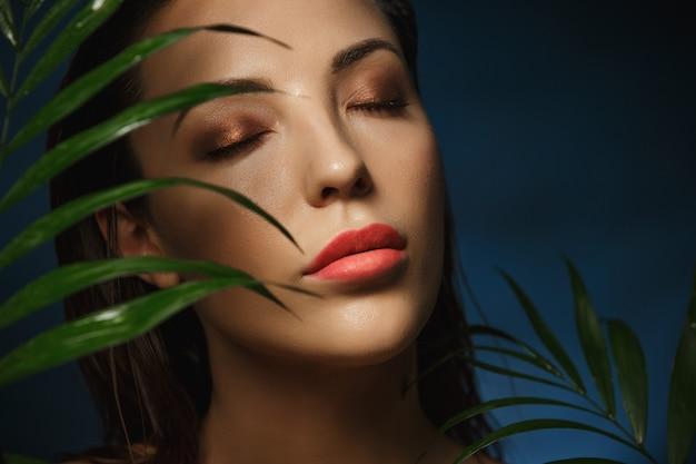Mooie vrouw gezicht onder exotische groene bladeren. modefotografie.
