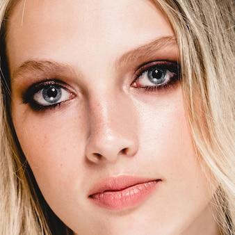 Mooie vrouw gezicht portret schoonheid huidverzorging concept met lang blond haar. fashion beauty model met mooi kapsel over grijze achtergrond