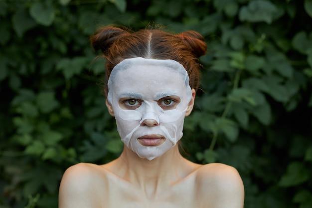 Mooie vrouw gezichtsmasker vooraanzicht schone huid cosmetologie groene struiken