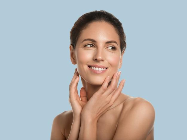 Mooie vrouw gezonde huid schoonheid gezicht cosmetische concept aanraken van haar gezicht kleur achtergrond. blauw.