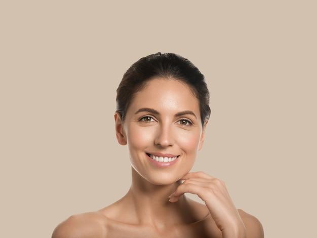 Mooie vrouw gezonde huid schoonheid gezicht cosmetische concept aanraken van haar gezicht kleur achtergrond. bruin.