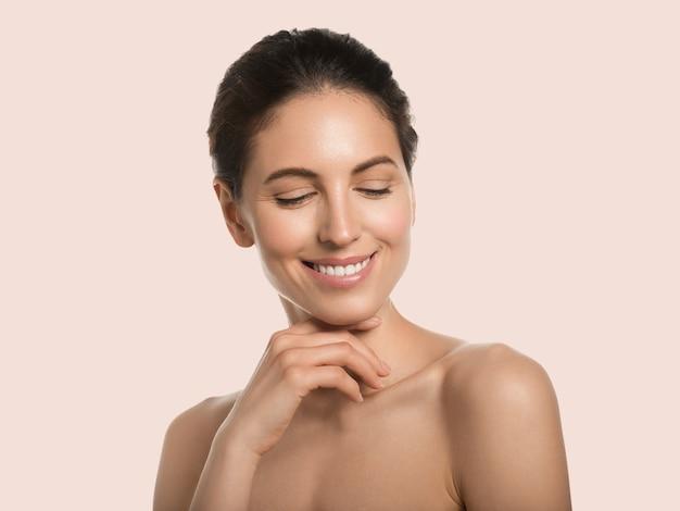 Mooie vrouw gezonde huid schoonheid gezicht cosmetische concept aanraken van haar gezicht kleur achtergrond. roze