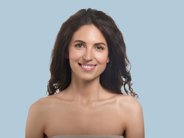 Mooie vrouw gezonde huid schoonheid gezicht cosmetische concept kleur achtergrond blauw. lang gekruld haar.