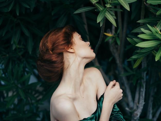 Mooie vrouw glamour groene bladeren luxe poseren buitenshuis.