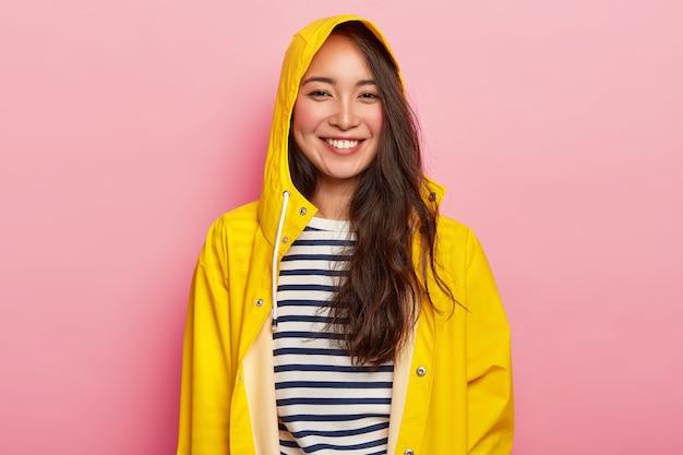 Mooie vrouw glimlachend geniet van het dragen van warme gestreepte trui, gele regenjas met capuchon, heeft een goed humeur, gaat uit met vrienden tijdens regenachtige dag