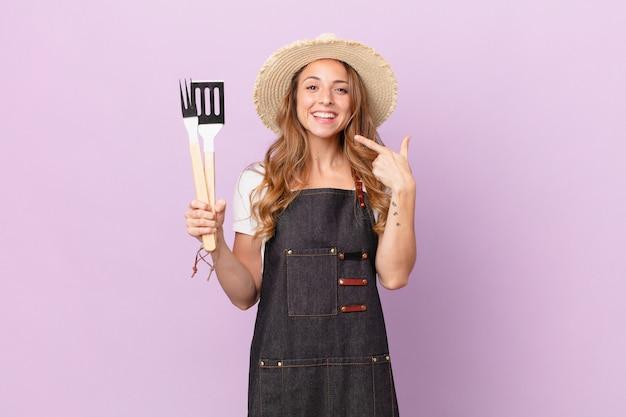 Mooie vrouw glimlachend vol vertrouwen wijzend naar eigen brede glimlach. barbecue chef-kok concept