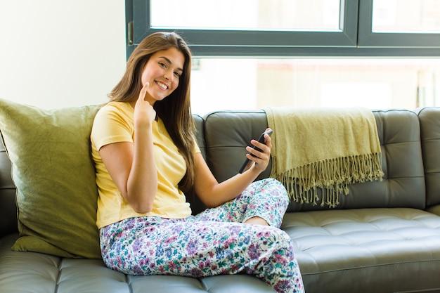 Mooie vrouw glimlachend vol vertrouwen wijzend op eigen brede glimlach, positieve, ontspannen, tevreden houding