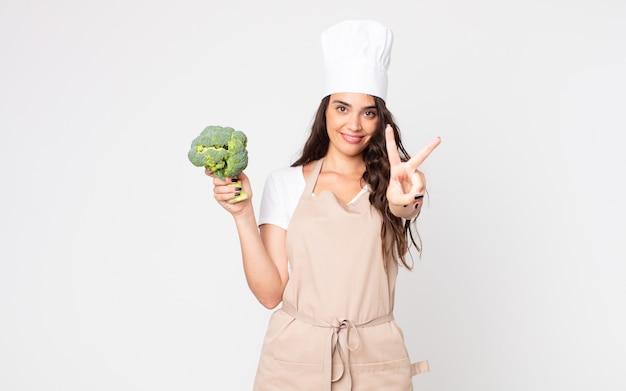 Mooie vrouw glimlacht en ziet er gelukkig uit, gebaart overwinning of vrede die een schort draagt en een broccoli vasthoudt